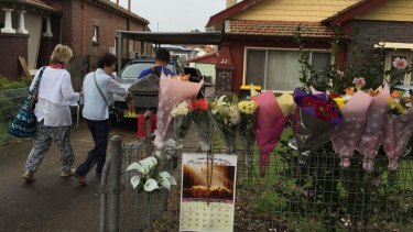 Bouquets of flowers line the fence of the Chans' house in Enfield as Michael and Helen Chan arrive home from Indonesia.