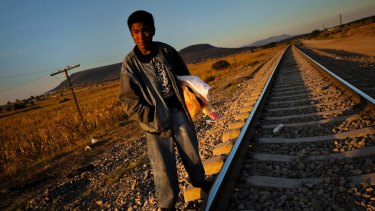 A Guatemalan asylum seeker waits on railroad tracks to climb on a cargo train bound for Mexico and the US.