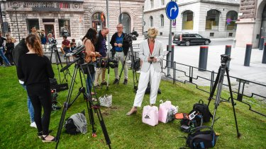 Reporters wait outside Rosenbad, the Swedish government headquarters in Stockholm, after the opposition united to demand no-confidence votes against three cabinet ministers.