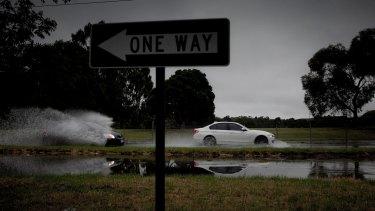 Cars driving through flash floods on Burwood Highway on Sunday.