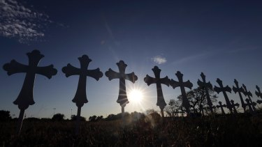 The sun sets behind 26 crosses placed in a field before a vigil for the victims of the First Baptist Church shooting.