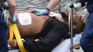 Khalid Masood is treated by emergency services outside parliament.