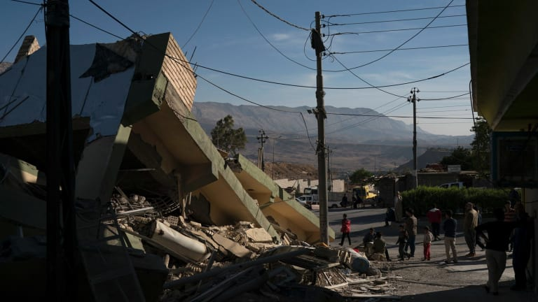 People walk next to a destroyed house after an earthquake in the city of Darbandikhan, northern Iraq, on Monday.