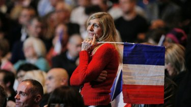 A woman holds a French national flag during a presidential campaign rally in Paris on Monday.