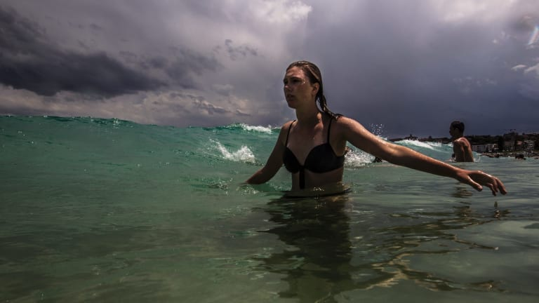 A swims at Bondi Beach as an afternoon storm approaches on Christmas Eve. Bondi is forecast for a top of 20 degrees on Christmas Day.
