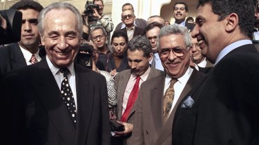 Then: Israeli Foreign Minister Shimon Peres, left, is all smiles along with PLO negotiator Mahmoud Abbas, second from right, in Cairo, in 1993.