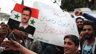"""Pro-government protesters hold a portrait of President Basharal- Assad and a placard that reads, """"Down with everyone who cooperated and supported the American aggression"""" in Damascus on Tuesday."""