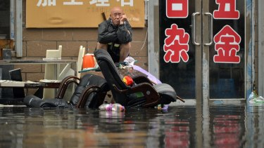 A man sits outside of a flooded shop in Shenyang in north-eastern China's Liaoning Province.