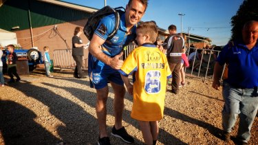 Two sides to the story: Josh Reynolds gives a young fan his City jumper after the game in Wagga Wagga last weekend.