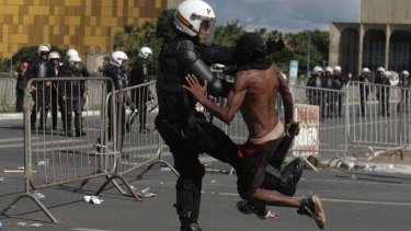 A demonstrator clashes with a police officer during an anti-government protest in Brasilia on Wednesday.