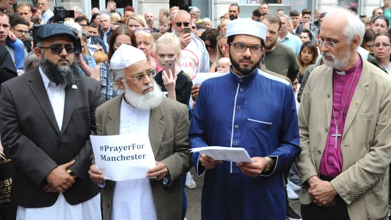 Members of the British Muslim Forum and religious leaders from Christian and Jewish faiths pay their respects at St Ann's square in Manchester on Sunday.