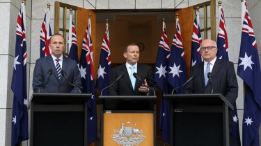 Tony Abbott appears with Peter Dutton and George Brandis in front of 10 flags at a press conference at which he criticised <i>Q&A</i>.