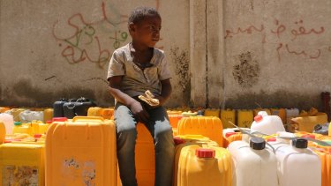 A Yemeni boy waits in line for water in Taiz. He begs for food and is eating bread he got from a nearby bakery.