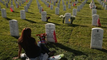 Dead remembered: Aileen Lucas visits the grave of her husband, US Marine Corps Major Christopher Lucas, on Veterans Day in Section 60.