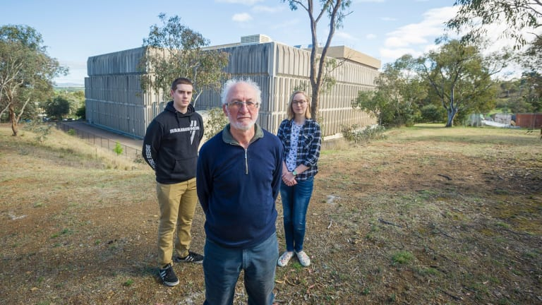 Local resident association members George Barrows, and Michaela Cully-hugill stand with Red Hill Regenerators' Michael Mulvaney. Standing behind the old Telstra building where the redevelopment will take place, destroying bushland and placing future residents next to contaminated land.