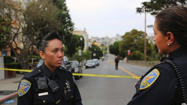 San Francisco Police Officer Grace Gatpandan speaks with another officer as they respond to reports of a shooting at Dolores Park in San Francisco.