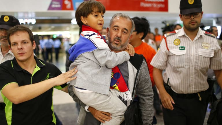 Syrian Osama Abdul Mohsen, centre, holds his son, Zaid, as they arrive at Barcelona train station on September 16.