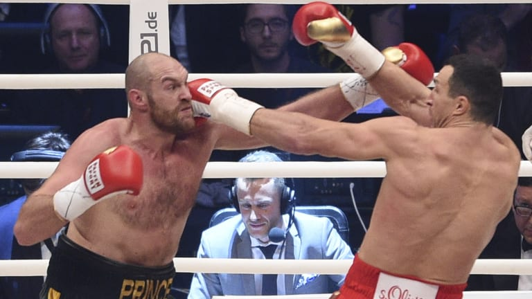Battle of the big men: Ukraine's Wladimir Klitschko, right, and Britain's Tyson Fury exchange blows in their world heavyweight title fight for Klitschko's WBA, IBF, WBO and IBO belts in the Esprit Arena in Duesseldorf, Germany.