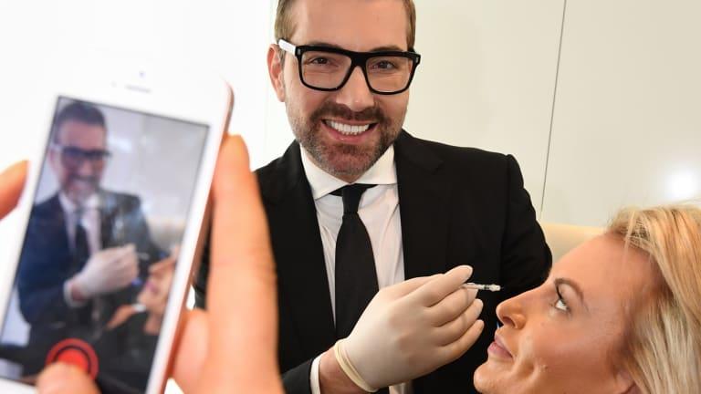 Snapchatting cosmetic surgeon Dr Kourosh Tavakoli with a staff member.