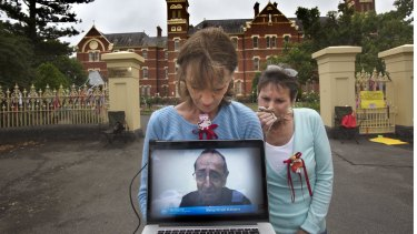 Gabrielle Short and Wendy Dyckhoff watch the live stream of Bishop Ronald Mulkearns testimony at the royal commission.
