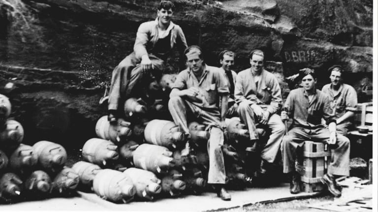 RAAF armourers sitting on a pile of mustard gas canisters in Glenbrook in 1944.