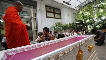 A Buddhist monk performs a blessing at a hospital in Bangkok as Thai family members  pray around the coffin of a victim of the Erawan Shrine bombing.