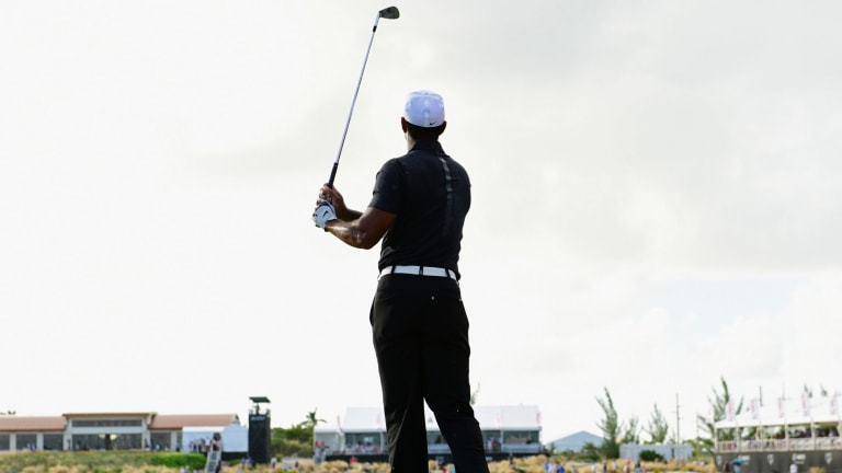 Tiger Woods watches his ball from the fairway.