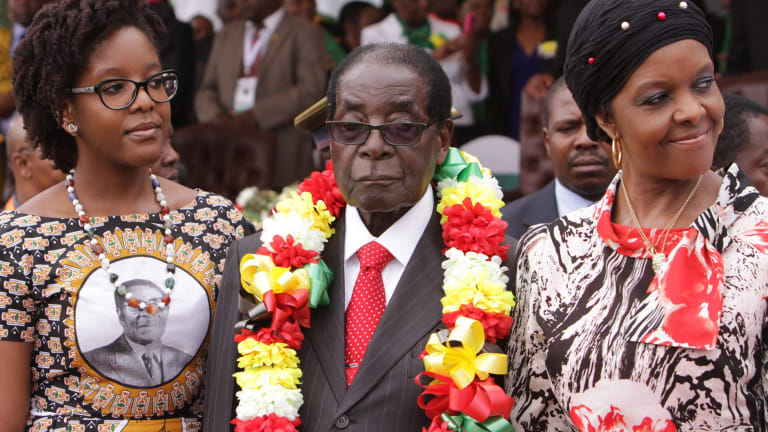 Zimbabwe's President Robert Mugabe is flanked by his daughter Bona and wife Grace during celebrations to mark his 91st birthday in the resort town of Victoria Falls on Saturday.