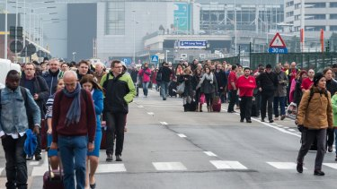 People walk away from Brussels airport after the blasts.