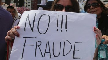 "A supporter of Guillermo Lasso holds a sign reading ""No to Fraud!"" during Monday's protest in Quito."