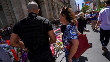 The armed man wandered among people laying flowers at the makeshift monument.