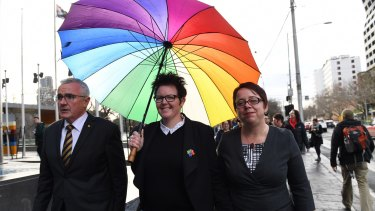 Mother-of-three Felicity Marlowe (centre) and her partner Sarah Marlowe with MP Andre Wilkie after appearing for a High Court injunction hearing application against the voluntary same-sex marriage postal survey.