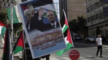 A poster of Palestinian President Mahmoud Abbas and PM Rami al-Hamdallah hangs on a street in Gaza City.
