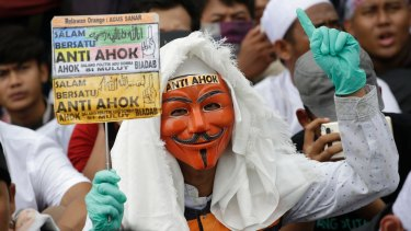 "A masked man holds an anti-Ahok sign during a protest against governor Basuki ""Ahok"" Tjahaja Purnama at the main business district in Jakarta, Indonesia."