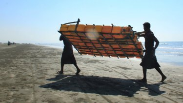 Rohingya fishermen carry a fishing raft, constructed with empty plastic containers, up the beach in Maungdaw, western Rakhine state, Myanmar. Their usual, sturdy fishing boats were outlawed three months ago.
