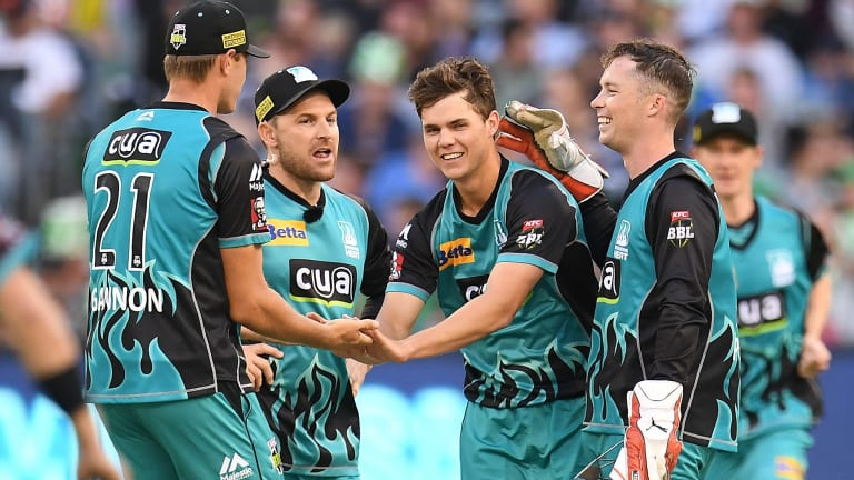 Mitchell Swepson (centre) celebrates with Heat teammates after taking a wicket against the Melbourne Stars.