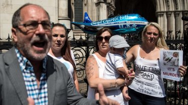 Supporters of Chris Gard and Connie Yates look on as Reverend Patrick Mahoney speaks to the media outside the High Court in London on July 10.