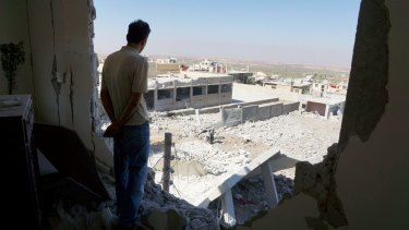 A man looks out from a ruined building in the Syrian town of al-Hara, in the southern province of Daraa, at what activists said was a site hit by barrel bombs dropped by government forces.
