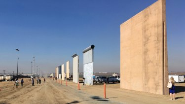 People look at prototypes for Trump's Mexico border wall in San Diego.