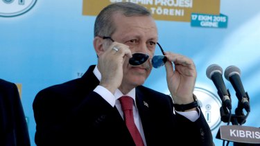 Turkish President Recep Tayyip Erdogan adjust his sunglasses before making a speech inaugurating an undersea pipeline to carry fresh water from Turkey to  northern Cyprus in the village of Mirtou.