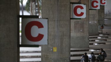 People wait at a deserted bus station after a protest in Brasilia on Friday.