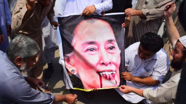 Pakistani protesters burn a caricature of Aung San Suu Kyi in a protest against ongoing violence against the Rohingya Muslim minority in Myanmar.