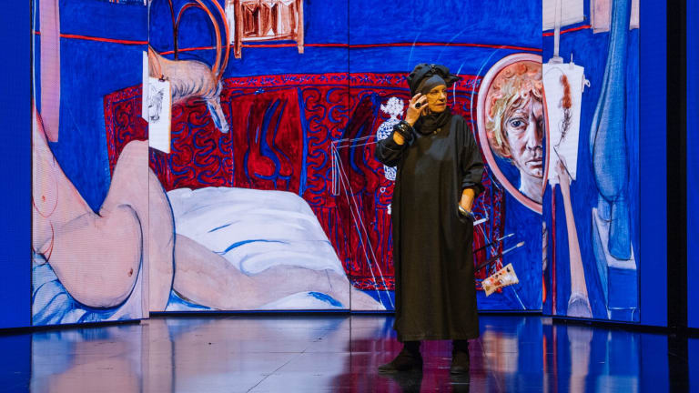 Wendy Whiteley standing in front of massive screens of Brett Whiteley's work at the launch of the Opera Australia season, which will include the opera Whiteley.