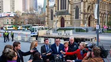 Premier Daniel Andrews speaks to the media as concrete bollards are installed at Federation Square in June.