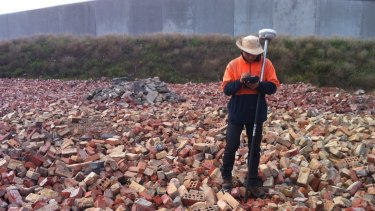A clean-up worker amid waste illegally dumped at a field in Prima Court, Tullamarine, by demolition company Monark Industries, trading as Hughes Demolition.