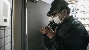 "Yautaka Kimura, left, and Akira Fujita pray after cleaning an apartment in Kawasaki, Japan, where a man had died about four months before his body was discovered. So-called ""lonely deaths"" happen frequently in Japan."