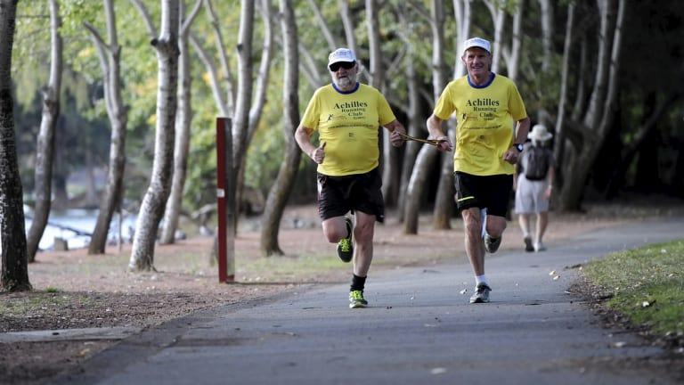 Local marathon runner, Peter Ralston of the Canberra chapter of Achilles International Australia, right, leading blind runner, Peter Granleese, who will be competing during the Canberra Running Festival.