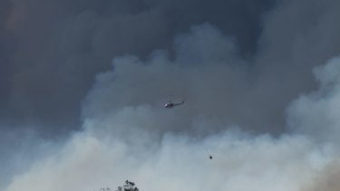 Strong winds fan bushfires:  A water bombing helicopter at work over the fire.