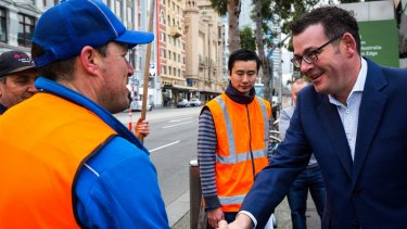 Premier Daniel Andrews greets construction workers in Federation Square.