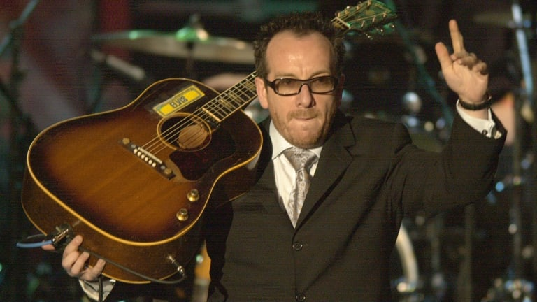 Elvis Costello waves to the audience after performing  during the Rock and Roll Hall of Fame induction ceremony in 2003, at New York's Waldorf Astoria.
